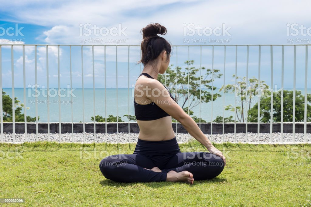 c5fbee9fa3b Happy Asian woman wearing black sport wear practice yoga Seated Twist pose  with beautiful sea