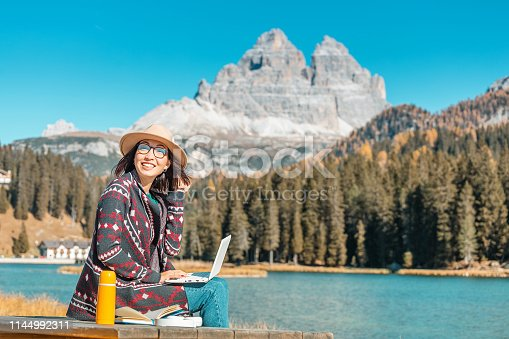 Happy Asian woman working on laptop on mountain lake background in autumn. The concept of remote work and freelancer