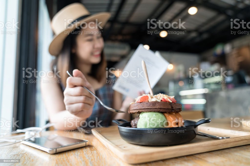 Happy asian woman's traveller wearing dress with brown hat sitting and eating ice cream with chocolate waffles ontop with almond and fruit serve on wooden plate in dessert café while reading a book. stock photo