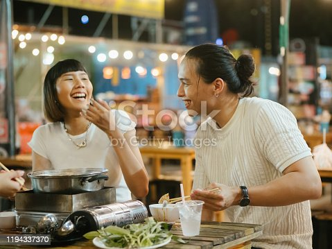 Happy asian friends cheering and toasting with traditional food at dinner outdoor in flea market. Bangkok, Thailand.