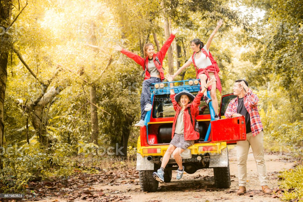 Happy asian young travellers with 4WD drive car off road in forest, young couple looking for directions on the map and another two are enjoying on 4WD drive car. Young mixed race Asian woman and man. stock photo