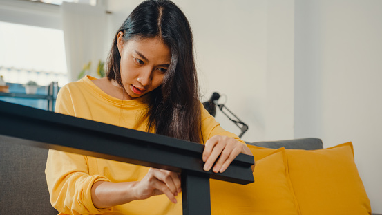 Happy asian young woman unpacking box and reading the instructions to assemble new furniture decorate house build table.