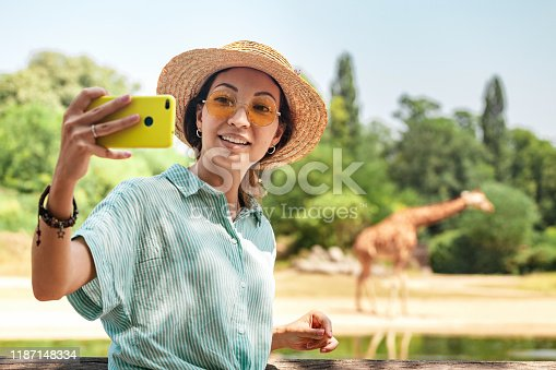 istock Happy asian zoology student girl taking selfie photo on smartphone while giraffe drinking from lake 1187148334