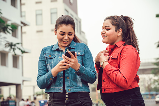 Happy Asian/Indian young women sharing mobile phone together and using smartphone.