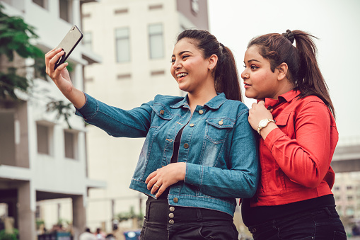 Happy Asian/Indian young women taking selfie together using smartphone.