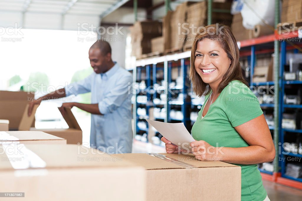Happy assembly line workers labeling packages in shipping distribution warehouse royalty-free stock photo