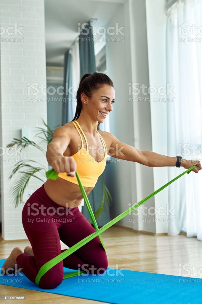Glückliche Athletin trainiert mit einem Powerband in ihrem Wohnzimmer. - Lizenzfrei Abnehmen Stock-Foto