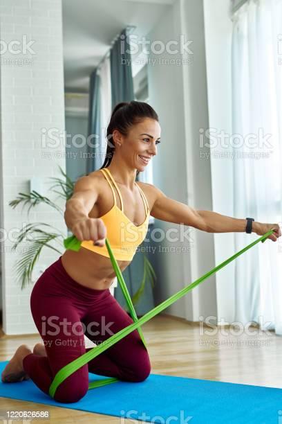 Glückliche Athletin Trainiert Mit Einem Powerband In Ihrem Wohnzimmer Stockfoto und mehr Bilder von Abnehmen