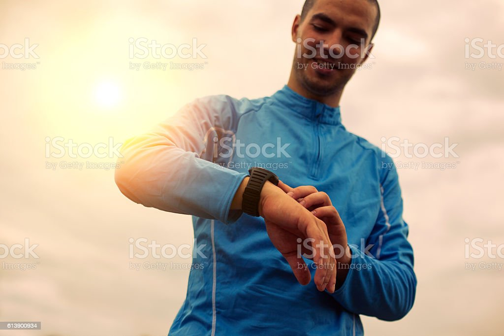 Happy athlete is looking at smart watch, sunlight effect – Foto