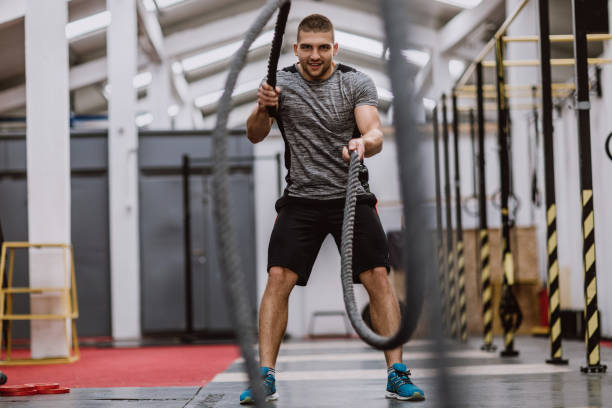 Happy Athlete Man Doing Battle Ropes stock photo