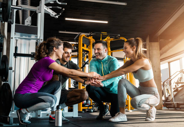 Happy athletes joining hands in unity in a gym Happy athletes joining hands in unity in a gym training equipment stock pictures, royalty-free photos & images