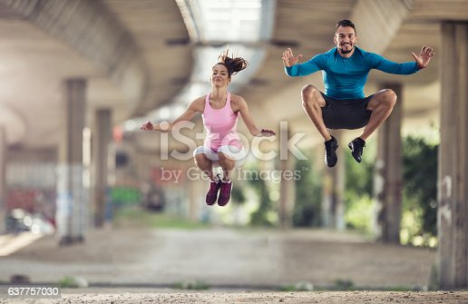 istock Happy athletes jumping high up on sports training outdoors. 637757030