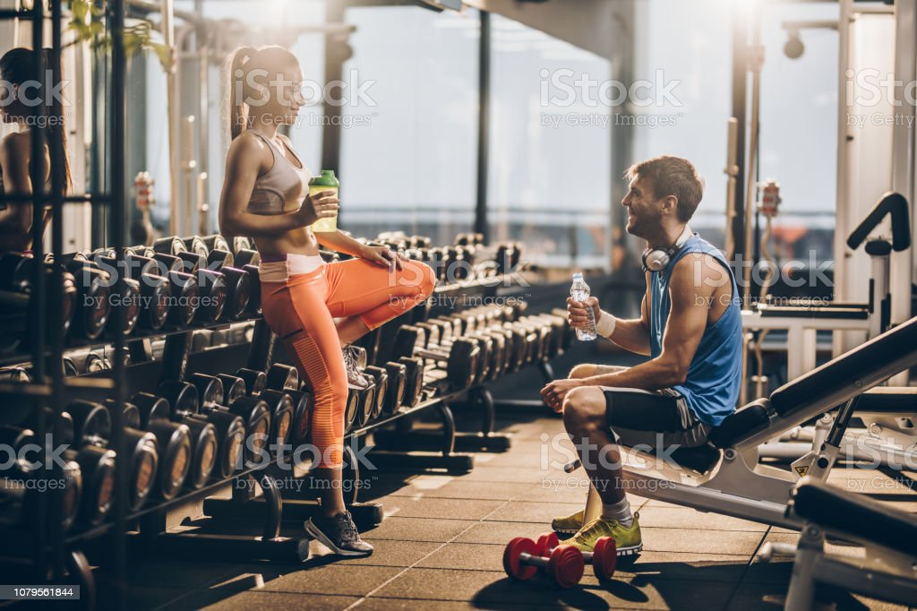 Happy athletic couple talking to each other after finishing sports...