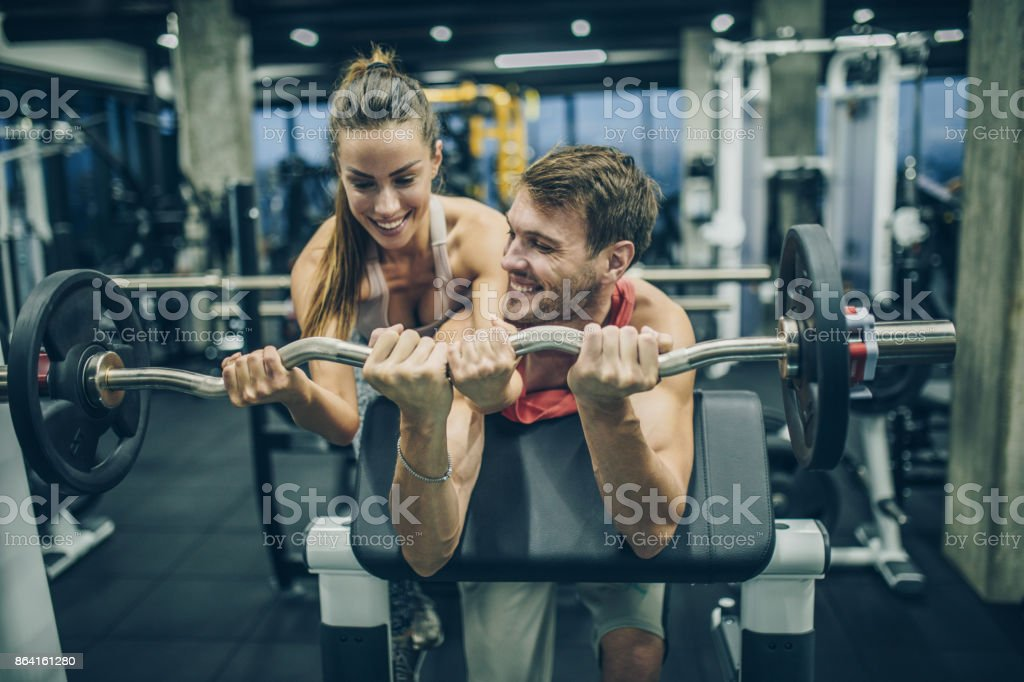 Happy athletic couple cooperating while exercising with barbell in a gym. royalty-free stock photo