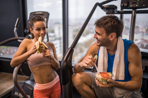 istock Happy athletic couple eating healthy food on a break in a gym. 855725196