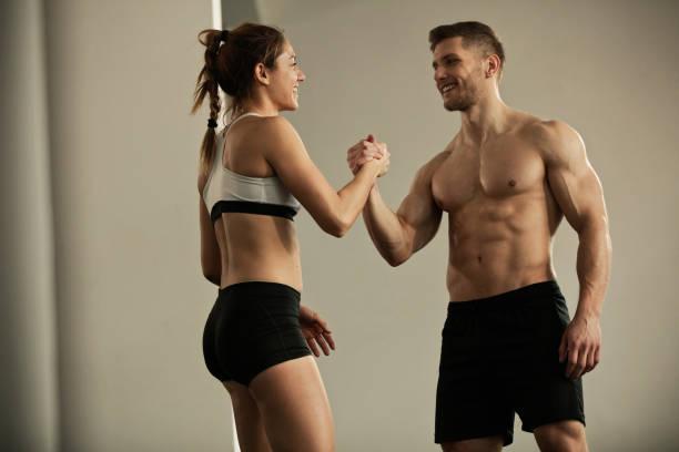 快樂的一對運動的夫婦在健身房互相問候。 - 肌肉發達 個照片及圖片檔