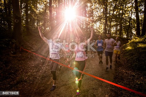 istock Happy athletic couple holding hands while running through finish line together. 849719428