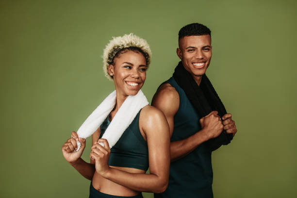 Happy athletic couple standing together holding towels stock photo