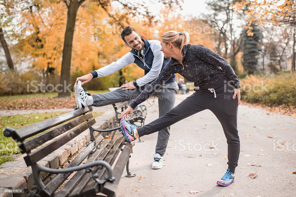 Happy athletic couple stretching their legs on a bench. stock photo