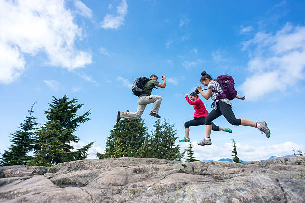 Happy, Athletic Hiking Family Jumping on Mountain Top with Backpacks stock photo