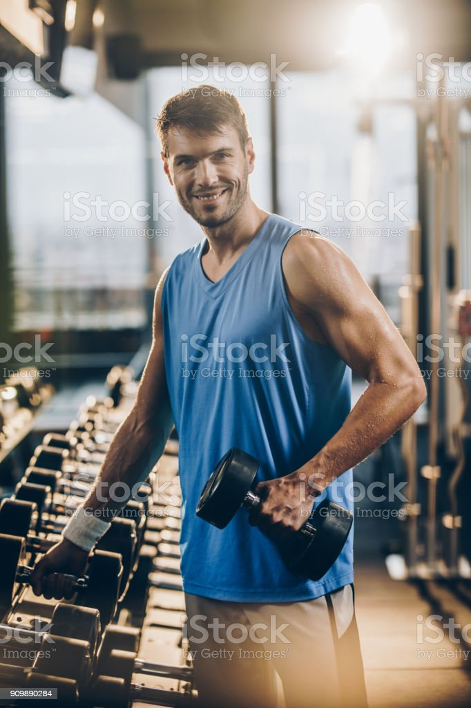 Happy athletic man taking weights from the rack in a health club. stock photo
