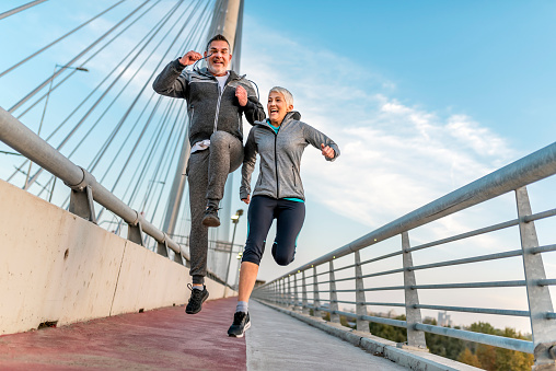 Happy athletic mature couple jumping together