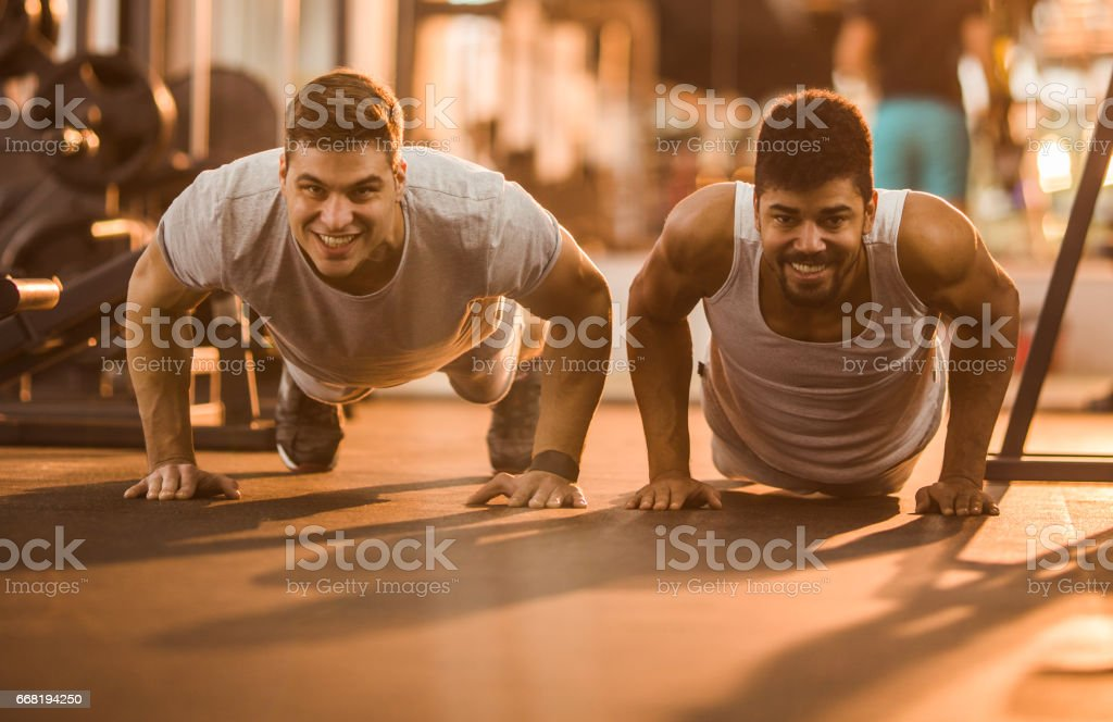 Happy athletic men exercising push-ups in a gym. stock photo
