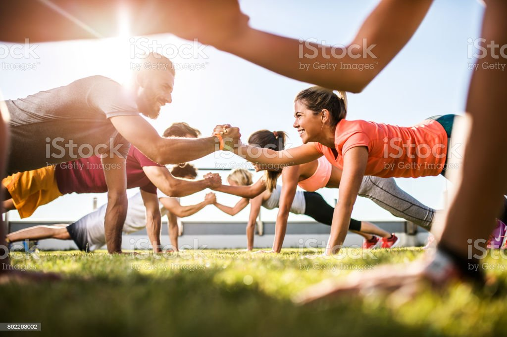 Happy athletic people cooperating while exercising on a sports training. stock photo