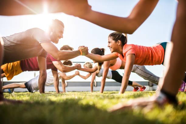 Gente atlética feliz cooperando mientras hace ejercicio en un entrenamiento deportivo. - foto de stock