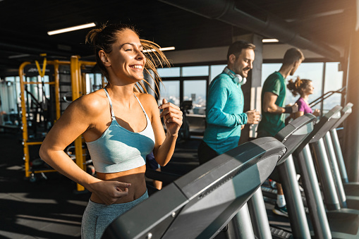 Happy athletic people jogging on treadmills in a health club