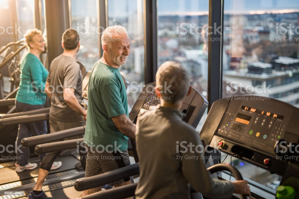 Happy athletic seniors talking while exercising on treadmills in a health club. stock photo