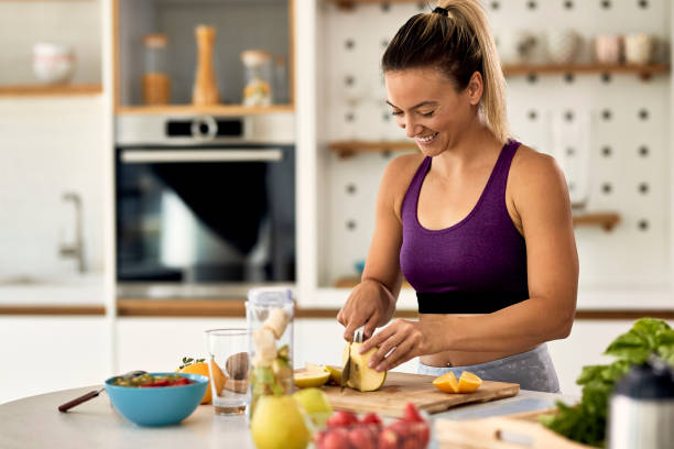Happy athletic woman cutting fruit while preparing healthy meal in the kitchen. stock photo