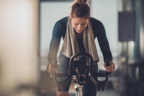 glückliche athletische frau radfahren auf dem heimtrainer in einem fitnessstudio. - herumwirbeln frau stock-fotos und bilder