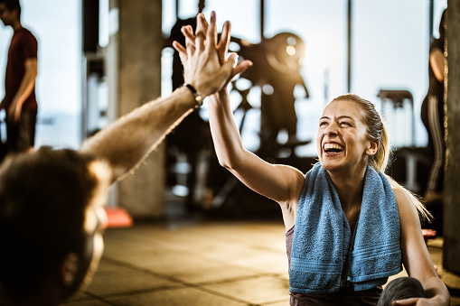 Happy female athlete having fun while giving her boyfriend high-five on a break in a gym.