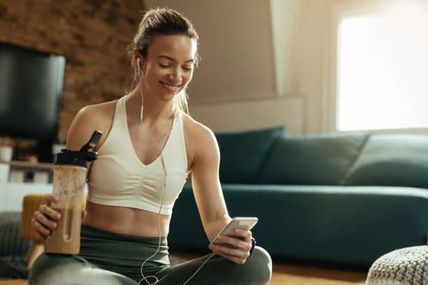 szczęśliwa atletyczna kobieta za pomocą telefonu komórkowego podczas picia smoothie w domu. - białko zdjęcia i obrazy z banku zdjęć
