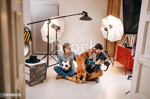 Working atmosphere in photographer studio, taking a shoot with model and dog