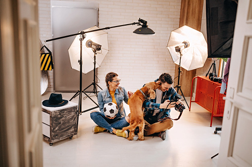 People and dog in a photoshoot studio doing valentine's day shots.