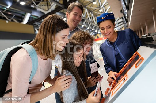 Happy attendant helping a family doing the self check-in at the airport using a machine and printing their boarding pass - travel concepts. **DESIGN ON BOARDING PASS WAS MADE FORM SCRATCH BY US**