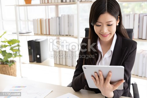 Happy Attractive businesswoman in black suit using a digital tablet while sit in desk at office building with natural light. Business and technology