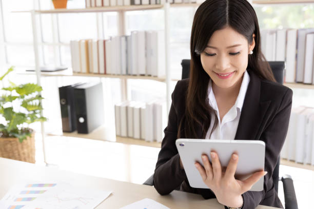 Happy Attractive businesswoman in black suit using a digital tablet while sit in desk at office building with natural light. Business and technology stock photo