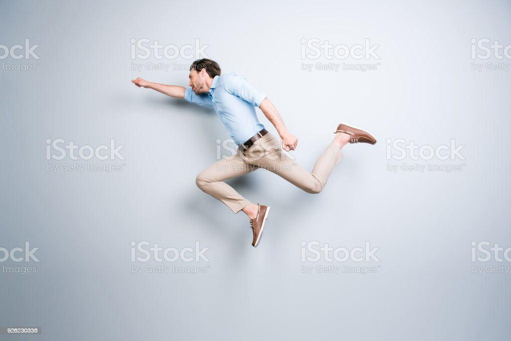 Happy, attractive, handsome, young, cool, joyful man with bristle jumping in air showing superman pose over grey background stock photo
