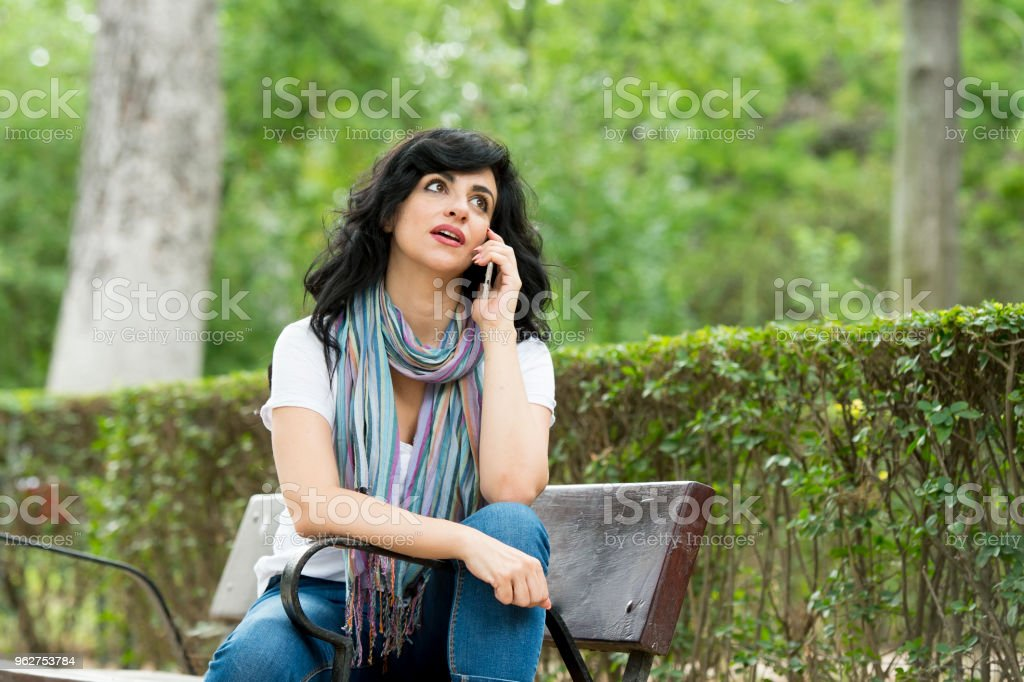 happy attractive latin woman wearing casual clothes sitting on a park bench texting and talking on her smart mobile phone in a green lush park or meadows - Foto stock royalty-free di Abbigliamento casual