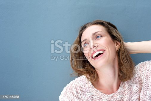 istock Happy attractive older woman smiling with hand in hair 470148768