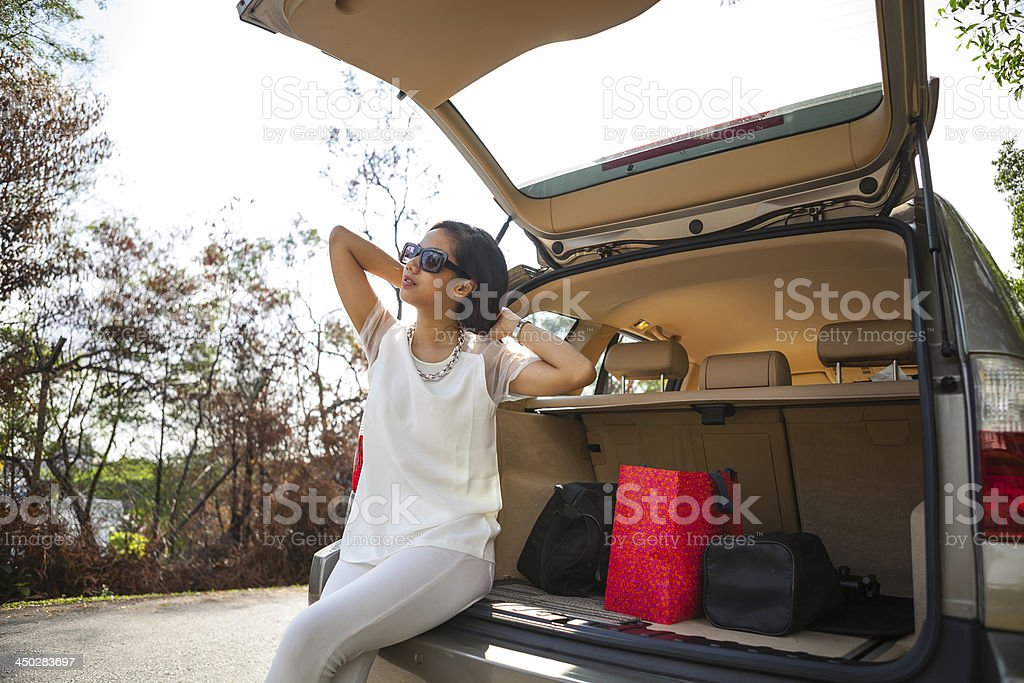 Happy attractive woman with sunglasses sitting in SUV trunk royalty-free stock photo
