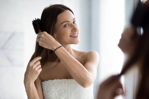 gelukkige aantrekkelijke jonge vrouw borstelen lang haar op zoek in spiegel - mirror mask stockfoto's en -beelden