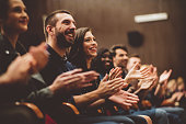Group of smiling people clapping hands in the theater, close up of hands. Dark tone.