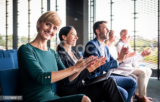 862720340 istock photo Happy audience applauding speaker at business conference 1202969127