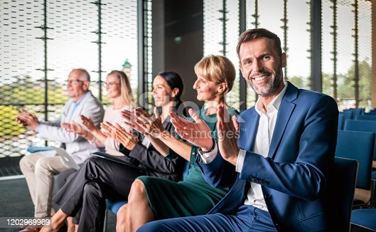 862720340 istock photo Happy audience applauding speaker at business conference 1202969969