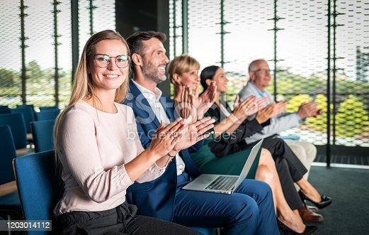 862720340 istock photo Happy audience applauding speaker at business conference 1203014112
