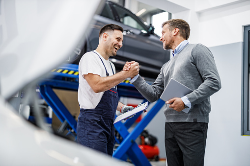 Happy mechanic and his foreman greeting each other with a manly handshake in auto repair shop.